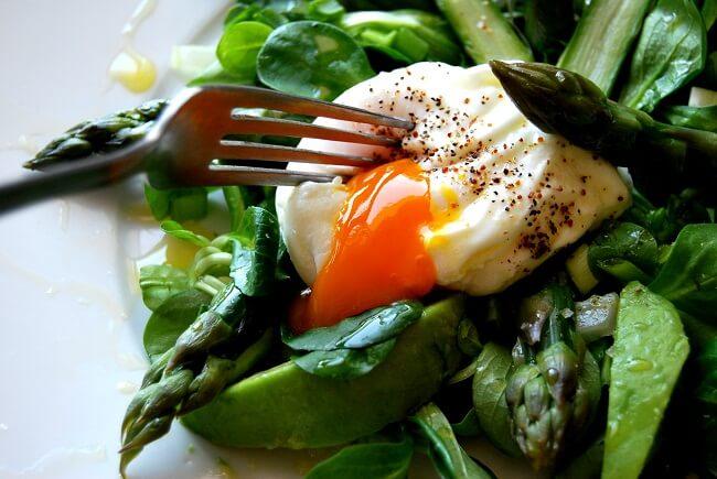 Jajko w koszulce w gniazdku z sałaty i szparagów